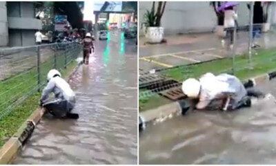 Watch: Dedicated KL Police Unclogs Drain Using His Own Hand During Flash Flood - WORLD OF BUZZ